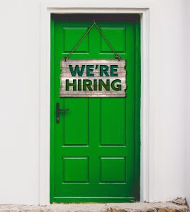 green door with sign we are hiring